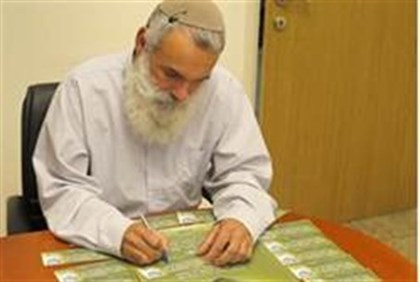 Rav Ronsky signs a card.