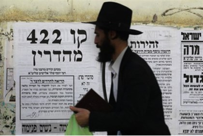 Hareidi man walks by poster regarding gender separation.