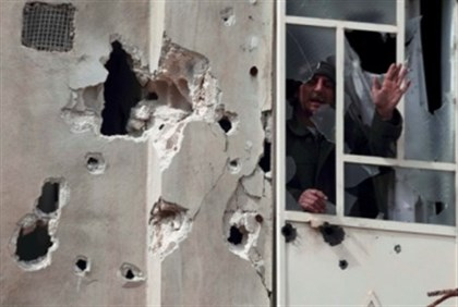 A man shouts from window afterr shelling by Assad's army