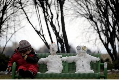 Snow men share bench with girl