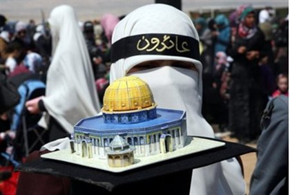 Activist holds a model of the Dome of the Rock at rally in Jordan