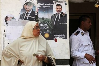 An Egyptian woman stands in front of posters of presidential candidates