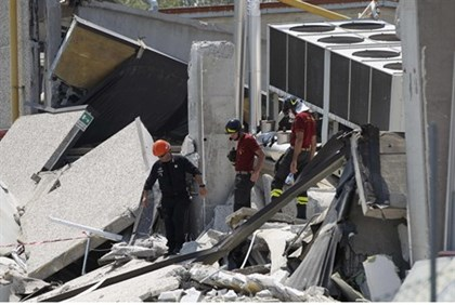 Rescue workers patrol a building which was damaged, after an earthquake, in Medolla near Modena May