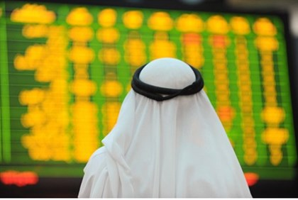 An Arab investor looks up at electronic boards displaying stock information