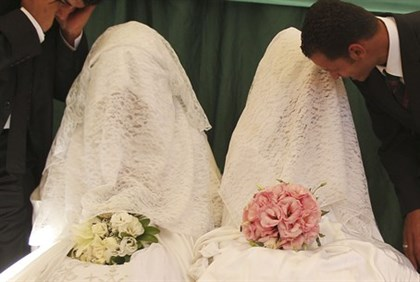 Arab brides speak to their grooms during a mass wedding ceremony