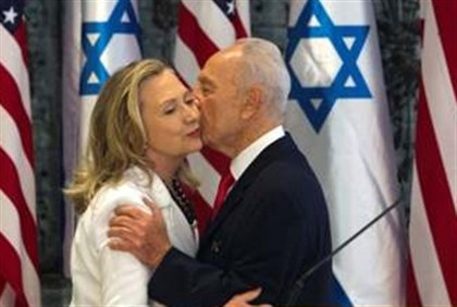 Clinton receives kiss on the cheek from Peres