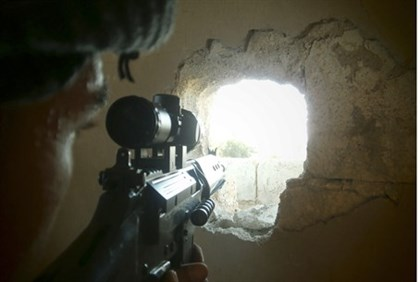 A member of the Free Syrian Army points his weapon through a hole in a wall