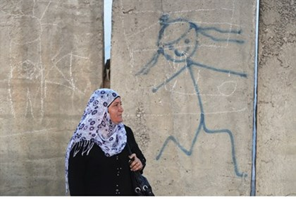 Arab woman stands in front of anti-Semitic caricature