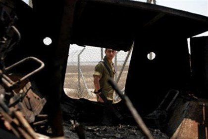An Israeli soldier walks past a burned Egyptian military vehicle that was seized by Islamist gunmen