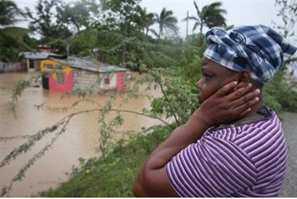 A woman surveys the damage of flooding to her home  as Isaac strikes Haiti