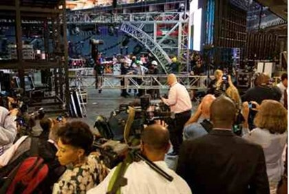 Media shoot video and photograph as workers prepare the Democratic party convention hall
