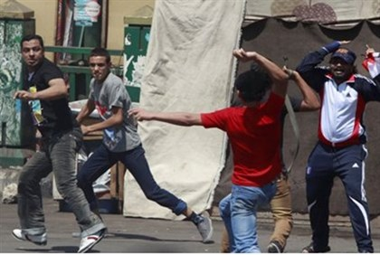 Supporter of Morsi (in red) clashes with anti-Mursi protesters in Tahrir Square