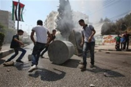 Arab youths erect a barricade in Hevron during a protest against the high cost of living