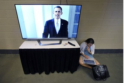 A delegate works on her computer next to a television depicting U.S. President Obama