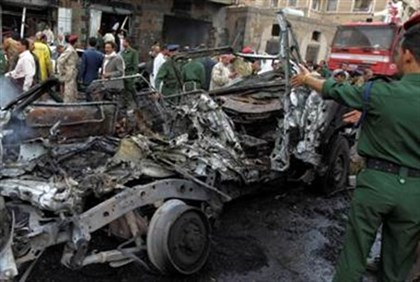 A soldier looks at a burnt vehicle at the scene of a car bomb explosion in Sanaa September 11, 2012.