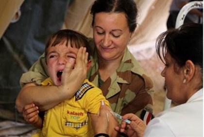 A Syrian boy cries as he gets an inoculation in a French military field hospital in Jordan