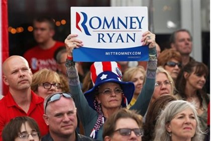 People listen to  Romney speak during a campaign rally at in Ohio