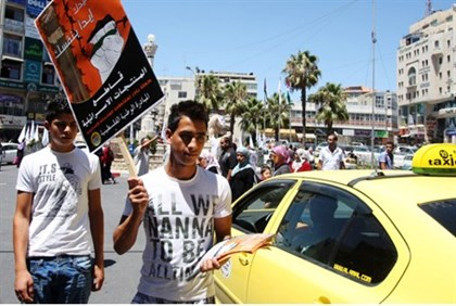 Man waves pro-boycott sign in Ramallah