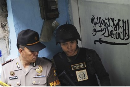 Indonesian police stand guard outside house of suspected terrorist