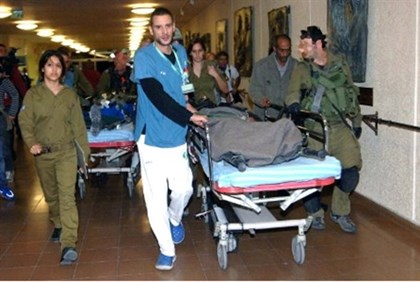 Wounded Israeli soldiers are wheeled into Soroka hospital.