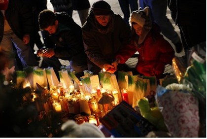 People light candles at a memorial for Sandy Hook Elementary School shooting victims in Newtown