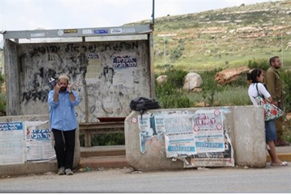 Israeli hitchhiker waits for a ride in Samaria