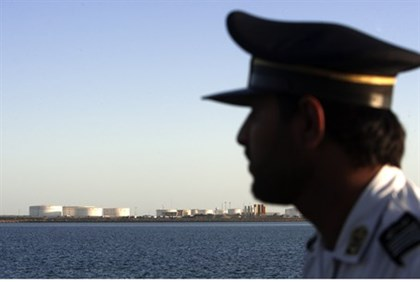 A security officer looks on at oil docks east of the Strait of Hormuz