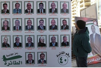 A man looks at electoral posters for parliamentary candidates in Amman
