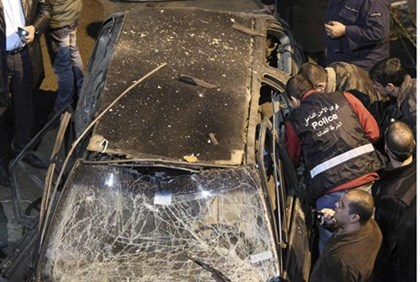 Security policemen inspect a damaged car in the suburbs of Beirut