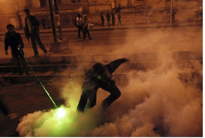 Anti-government protester hurls tear gas cannister in Cairo