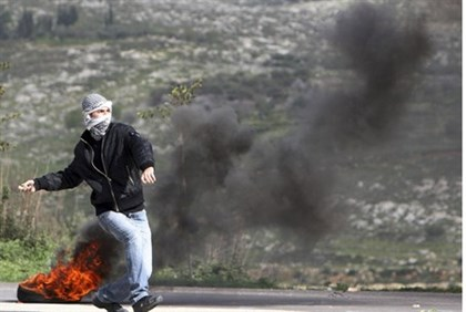 PA protester throws rocks towards Israeli forces near Shechem