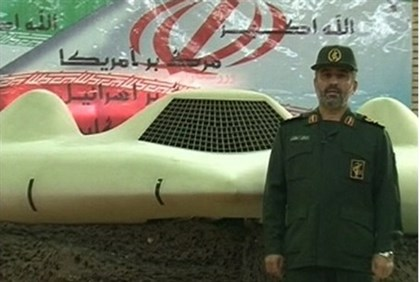IRGC aerospace force commander next to what Iran says is a captured U.S. drone plane