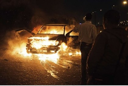 An Egyptian police car set ablaze on Cairo's Six of October Bridge