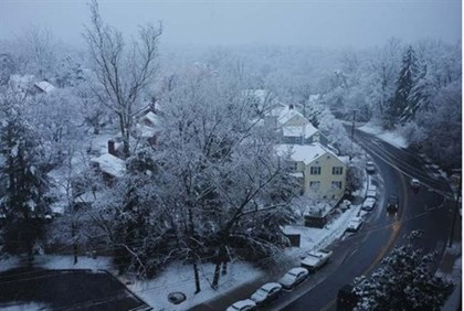 Snow falls over a residential neighbourhood