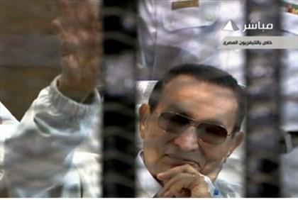 Hosni Mubarak waves from behind bars during his retrial