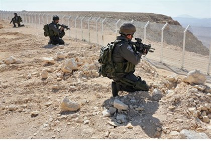 Israeli soldiers stand guard at Sinai border