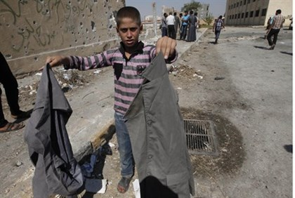 Syrian child holds school uniforms at the site of attack in Raqqa