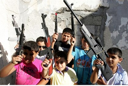 Palestinian children play with toy guns