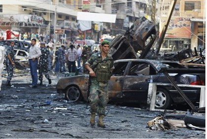 A Lebanese soldier stands at the site of a car bombing in Beirut, Aug. 16