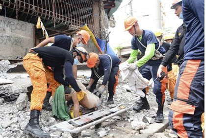 Rescue workers pull a body from the rubble fo a collapsed building in the Philippines