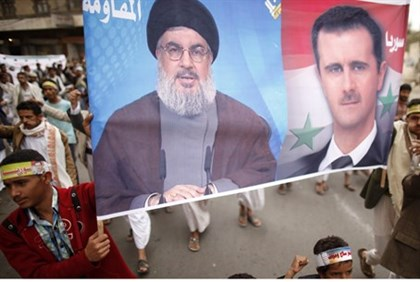 Shia Muslim demonstrators show their support for Hezbollah chief, Syrian President