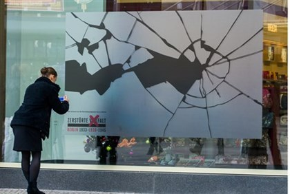 Woman affixes sticker to shop window as part of Kristallnacht memorial