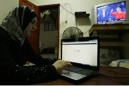 Woman uses computer in Gaza