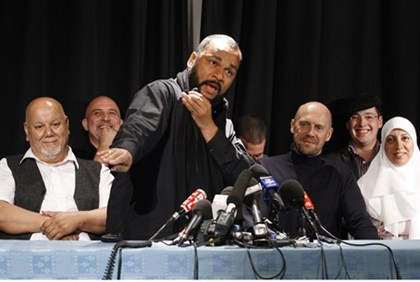 "Dieudonne performs the ""quenelle"" gesture at a news conference"