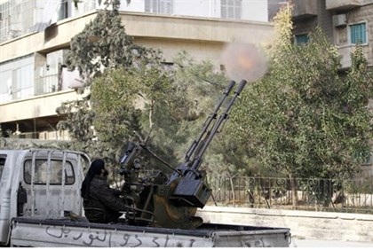 A fighter from the Al Qaeda-aligned Nusra Front fires a mounted machine gun