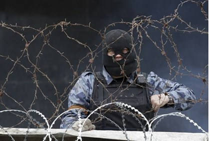 Pro-Russian militiaman behind a barricade at occupied gov't building in Donetsk