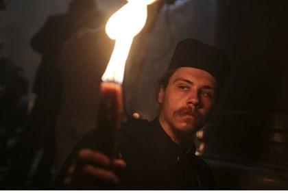 Orthodox Christian pilgrim holds a candle during Easter eve celebrations