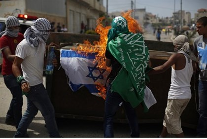 Protesters burn an Israeli flag during clashes with troops near Ofer Prison