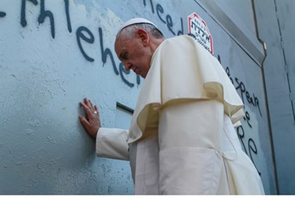 Apolitical? Pope Francis leans on security fence in prayer