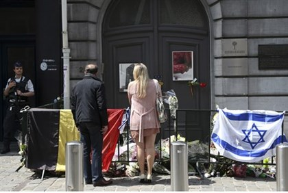 A couple stands by a memorial outside Brussels Jewish Museum